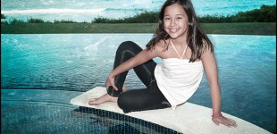 Young Girl On Edge of Hot Tub with Pool and Ocean in Background