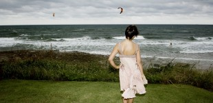 Young woman in fashion dress overlooking the ocean with a dramatic sky