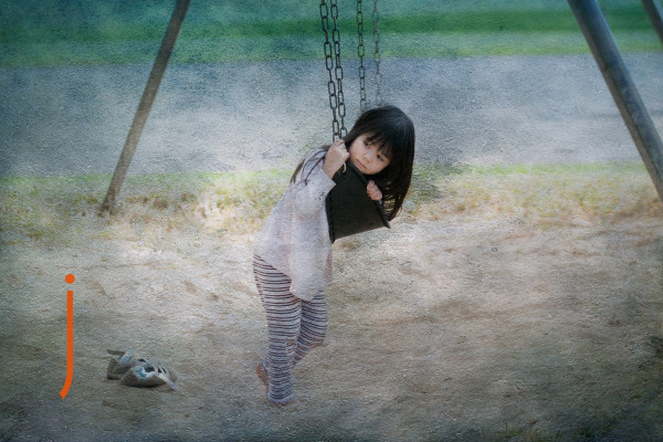 Portrait of young girl on a swing